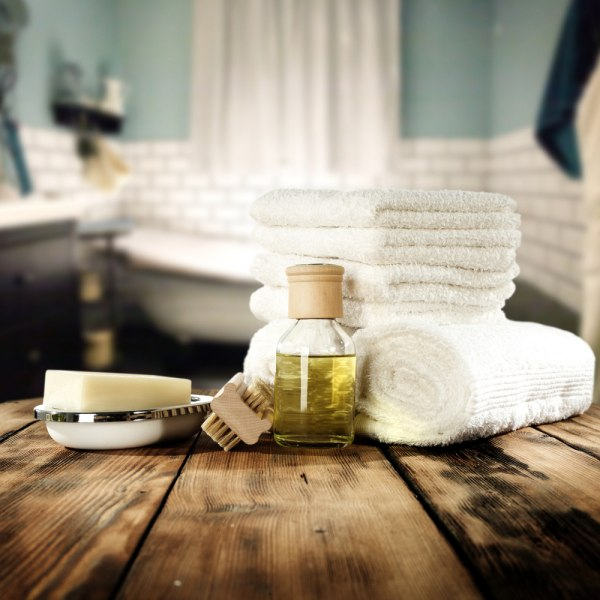 stack of towels, a bottle of oil, and other spa essentials for home