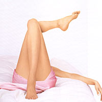 woman lying on the bed with legs crossed
