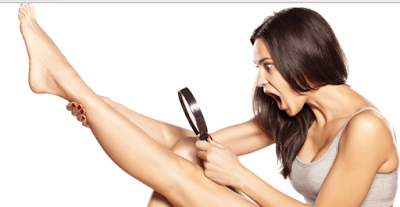 Woman looking at a magnifying glass in her raised leg