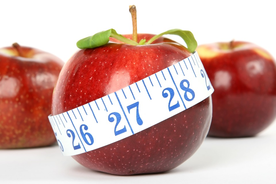 3 red apples, the center wrapped with a tape measure